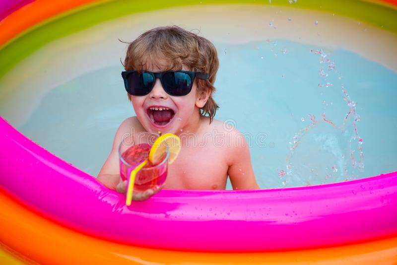Happiness. Summer rest. The child screams with pleasure. Laugh and smile. The boy in the pool. The child drinks a summer stock photo