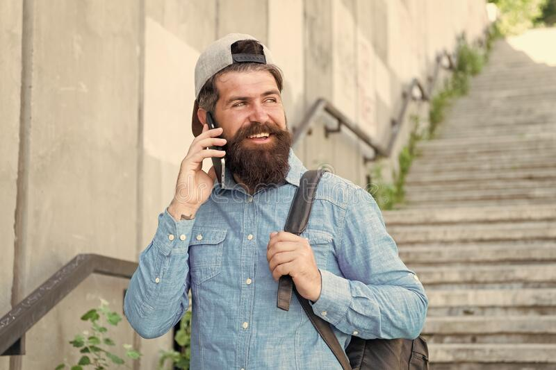 Happiness is traveling. Bearded man speak on phone. happy brutal man walk street. Male barber care. brutal hipster with stock image