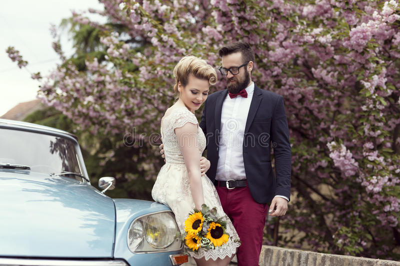 Happiness in two. Newlywed couple standing in the street next to an old retro car, hugging and embarking on a honeymoon stock image