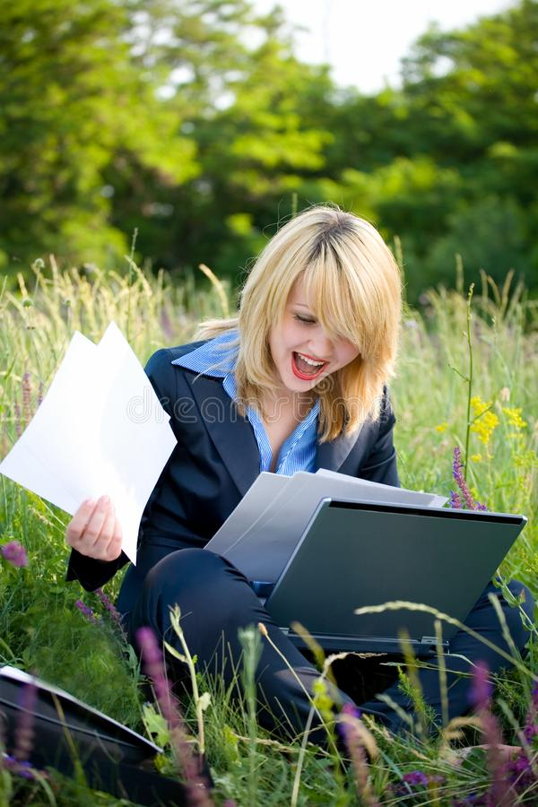Happiness woman on grass with documents royalty free stock photography