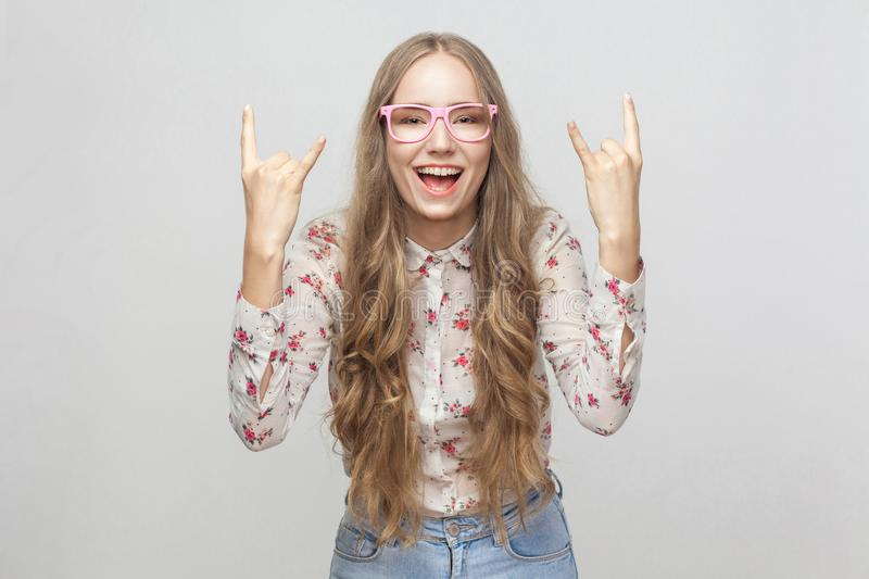 Happiness young adult girl, showing rock and roll fingers and lo. Oking at camera with crazy look. Studio shot, isolated on gray background stock image