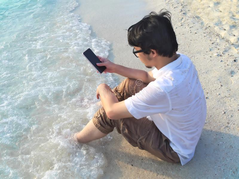 Happiness young Asian man with mobile smart phone sitting on sand of tropical beach. Summer vacations concept. Internet of things stock photo