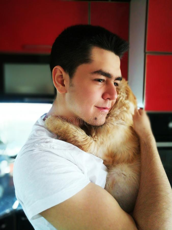 Happiness. Cat with Young Man. Orange Persian Cat. Lover Man, Hugging and Cuddling his Happy Domestic Cat Pet. Love to the animals. Happiness. Young attractive stock photos