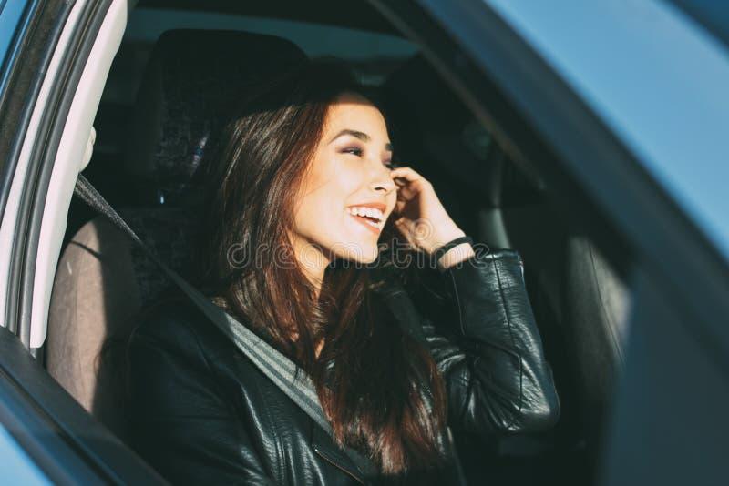Happpy美丽的迷人的深色的长发年轻亚裔妇女在黑皮夹克enjoing的生活中在车窗里 免版税库存照片