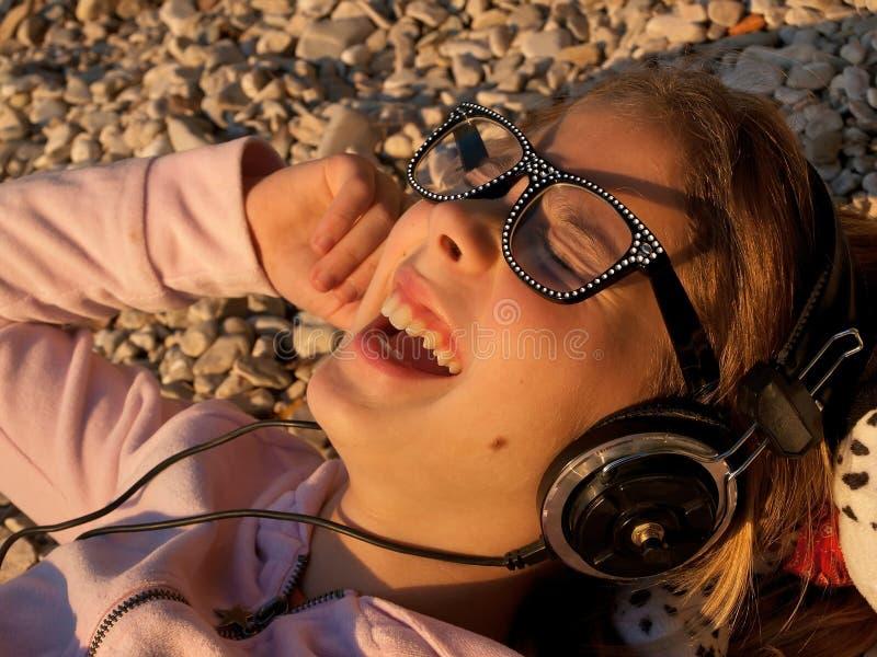 Happpy barn som lyssnar till musik arkivbild
