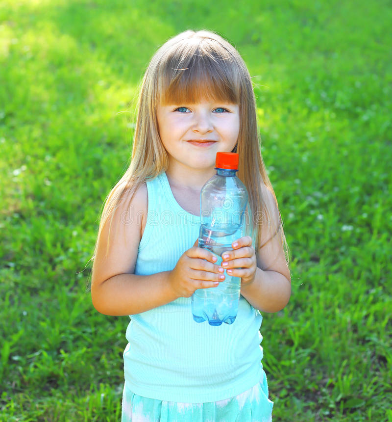 Happpy glimlachend kind en plastic fles met water royalty-vrije stock foto