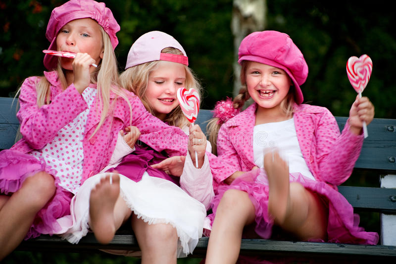 Happy 3 sisters. Happy children having pink clothes and a lollipop royalty free stock photos