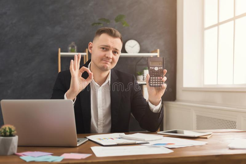 Happy financier man working at office desktop. Happy accountant showing calculator and ok sign at his workplace. Income growth, right marketing strategy concept stock image
