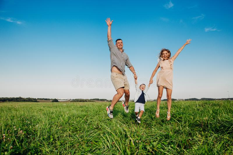 Happy family jumping together in the field in sunny day royalty free stock photo