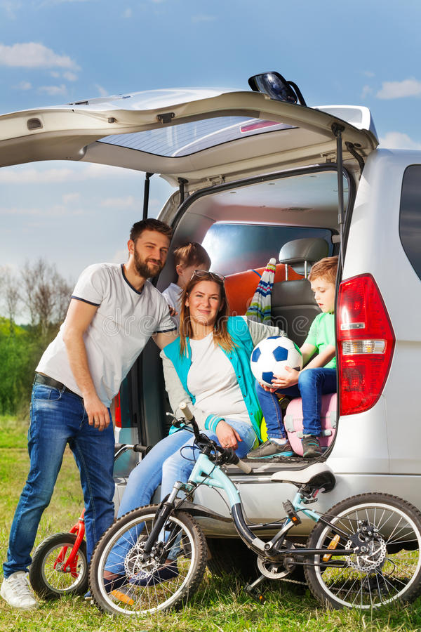 Happy active family on the nature vacation. Happy active family, mother, father and two boys, sitting in the luggage boot of their auto on the nature vacation stock photos