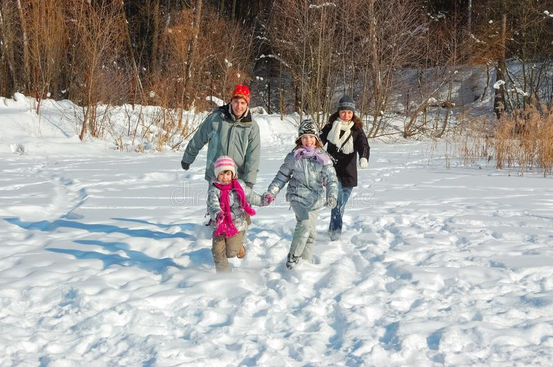 Happy family walks in winter, having fun and playing with snow outdoors on holiday weekend royalty free stock photography
