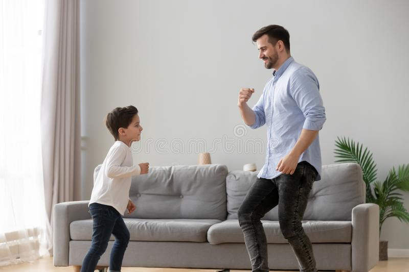 Happy dad and kid son dancing together in living room. Happy active family young dad and cute little kid son dancing having fun in living room together, funny royalty free stock images
