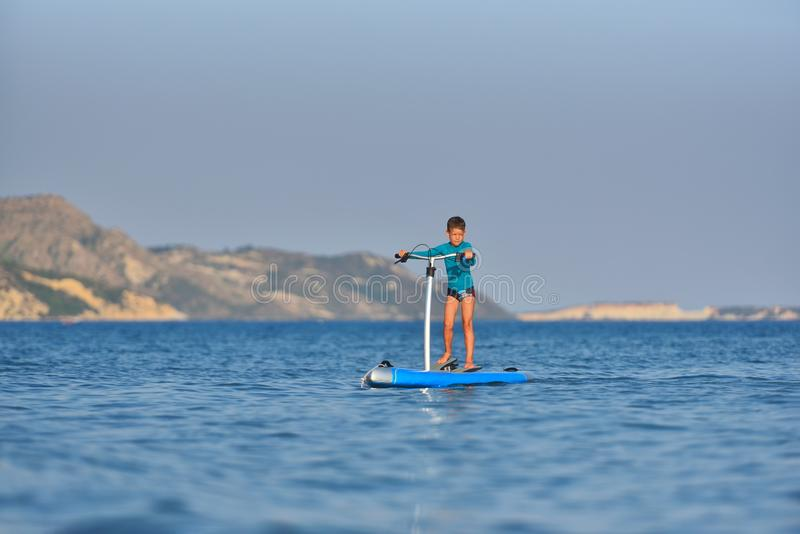Happy active kid on a Hobie Stand Up Paddle board stock images