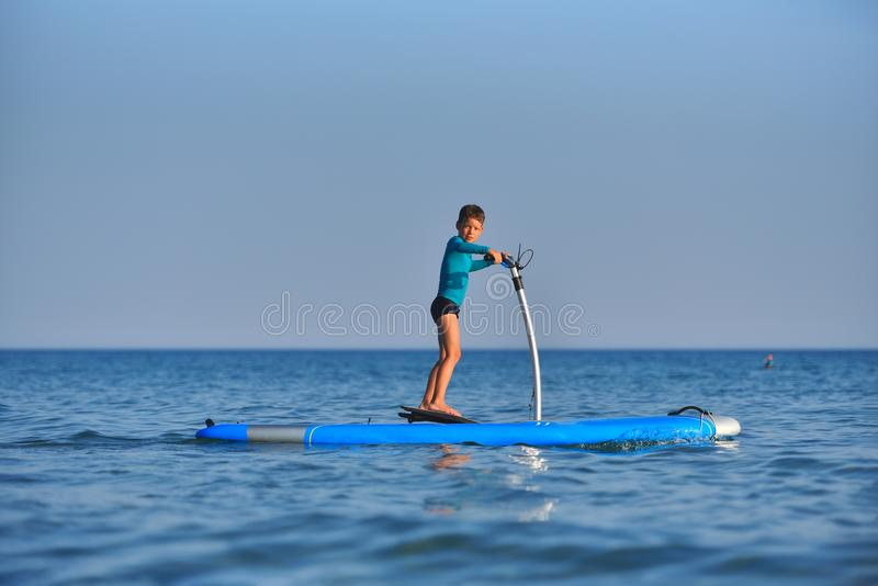 Happy active kid on a Hobie Stand Up Paddle board royalty free stock photo