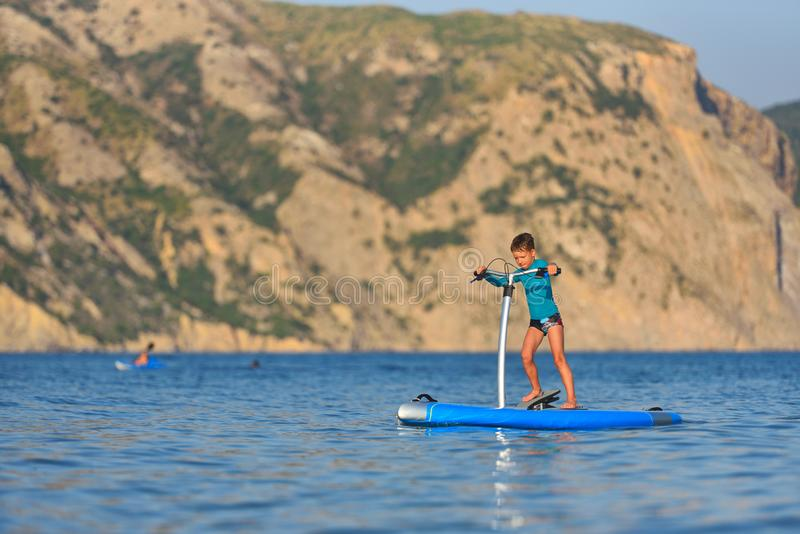 Happy active kid on a Hobie Stand Up Paddle board stock photo