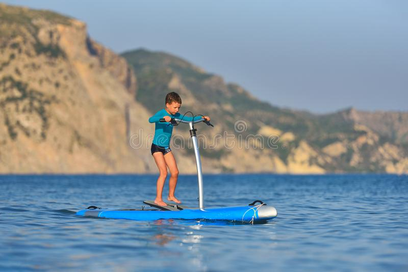 Happy active kid on a Hobie Stand Up Paddle board stock image