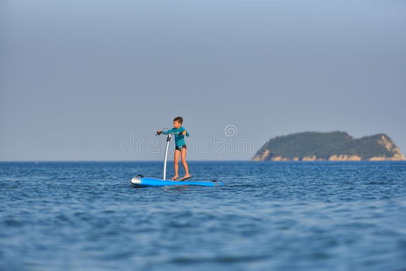 Happy active kid on a Hobie Stand Up Paddle board royalty free stock images