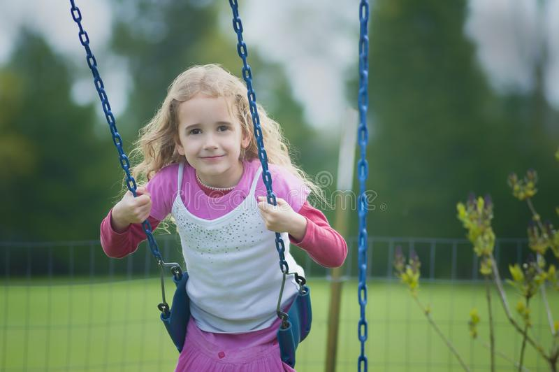 Close up of little girl swinging in swing royalty free stock images