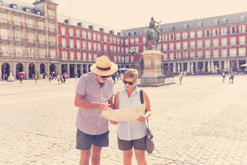 Happy senior couple looking for directions using a map on holidays in a European city. Happy active retired tourist couple searching for their location in Plaza stock image