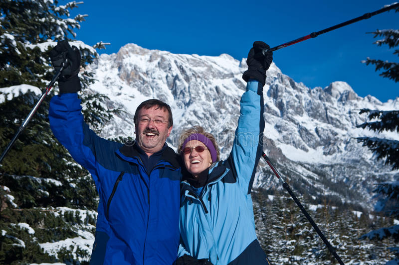 Happy active seniors. A senior couple in a winter setting in the alpine mountains. Active and happy seniors stock image