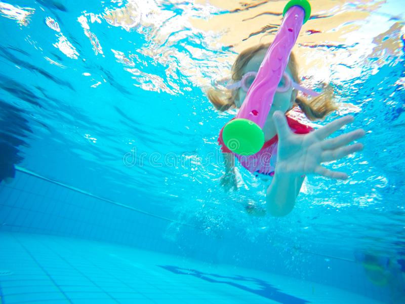 Happy active underwater child swims in pool, beautiful healthy girl swimming and having fun on family summer vacation, kids sport royalty free stock photo