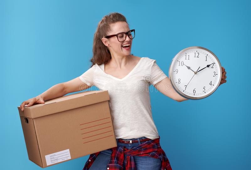Happy active woman with cardboard box looking at clock on blue royalty free stock images