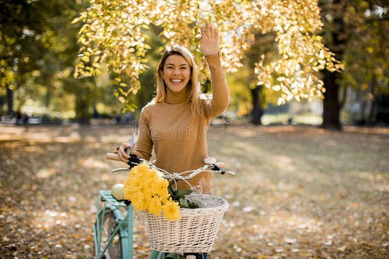Happy active woman riding bicycle in autumn park royalty free stock photography