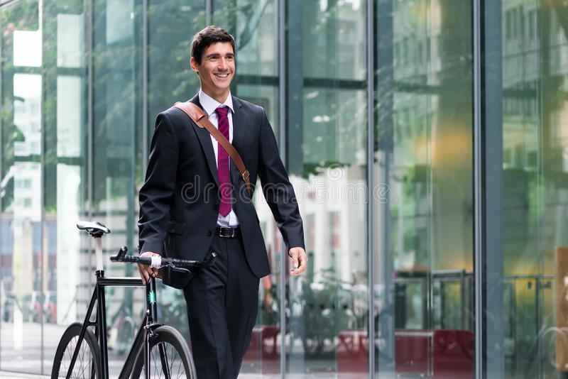 Happy active young man walking to the job after bicycle commutin stock photography