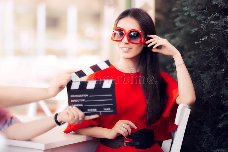 Happy Actress with Oversized Sunglasses Shooting Movie Scene. Diva in red dress and big shades starring in an artistic film stock photography