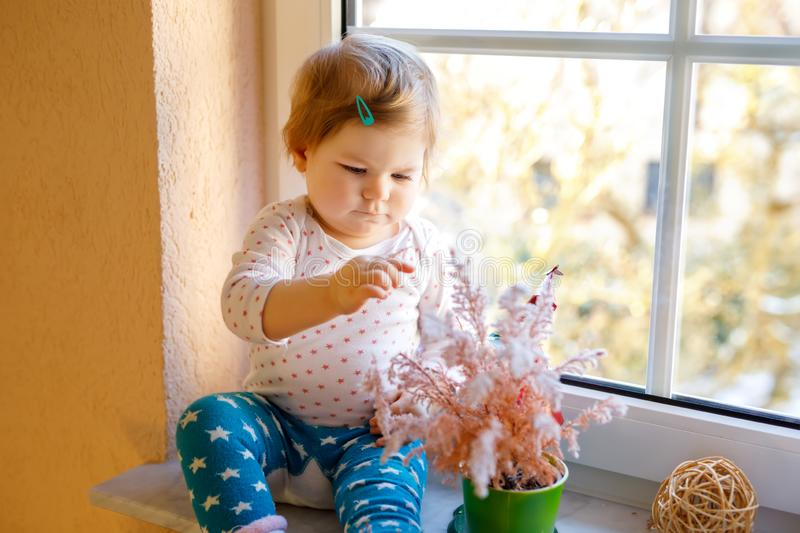 Happy adorable cute baby girl sitting near window and looking outside on snow on winter or spring day. Smiling child playing and looking interested and curious royalty free stock image