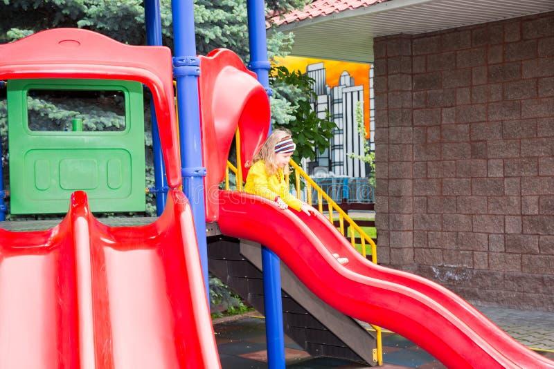 Happy adorable girl on children`s slide on playground near kindergarten Montessori on summer day. Happy adorable girl on a children`s slide on playground near royalty free stock images