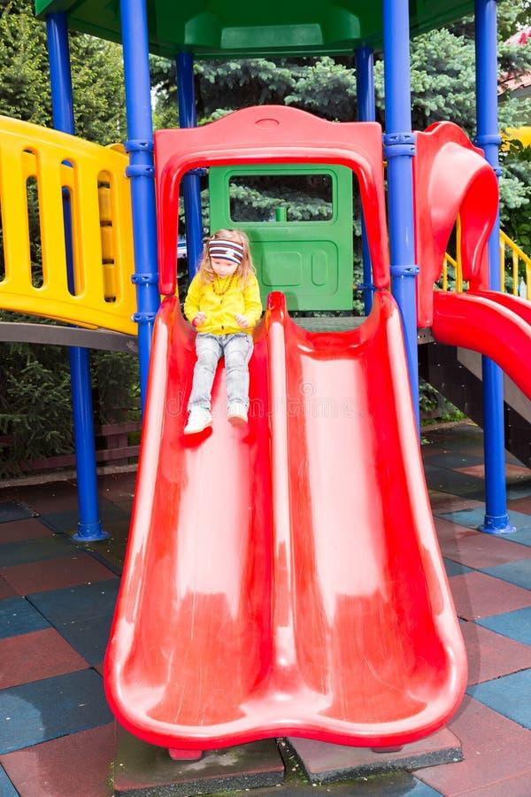 Happy adorable girl on children`s slide on playground near kindergarten Montessori on summer day. Happy adorable girl on children`s slide on a playground near stock photos