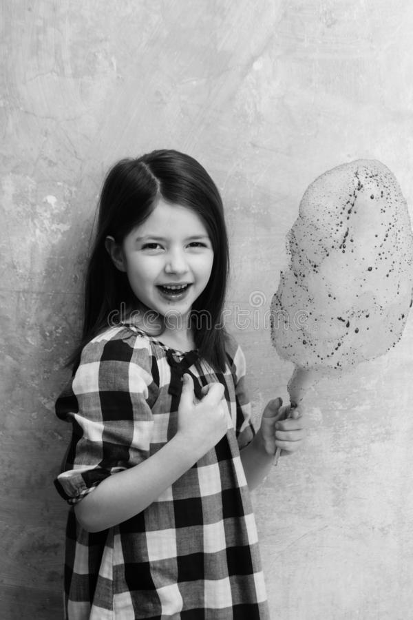 Happy adorable girl smiling with cotton candy on stick. Happy, adorable girl, small, little, child in plaid dress smiling with delicious, pink, cotton candy royalty free stock image