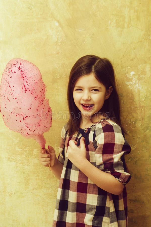 Happy adorable girl smiling with cotton candy on stick. Happy, adorable girl, small, little, child in plaid dress smiling with delicious, pink, cotton candy stock photography