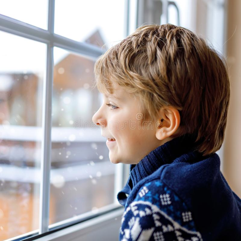Happy adorable kid boy sitting near window and looking outside on snow on Christmas day or morning. Smiling child royalty free stock photos