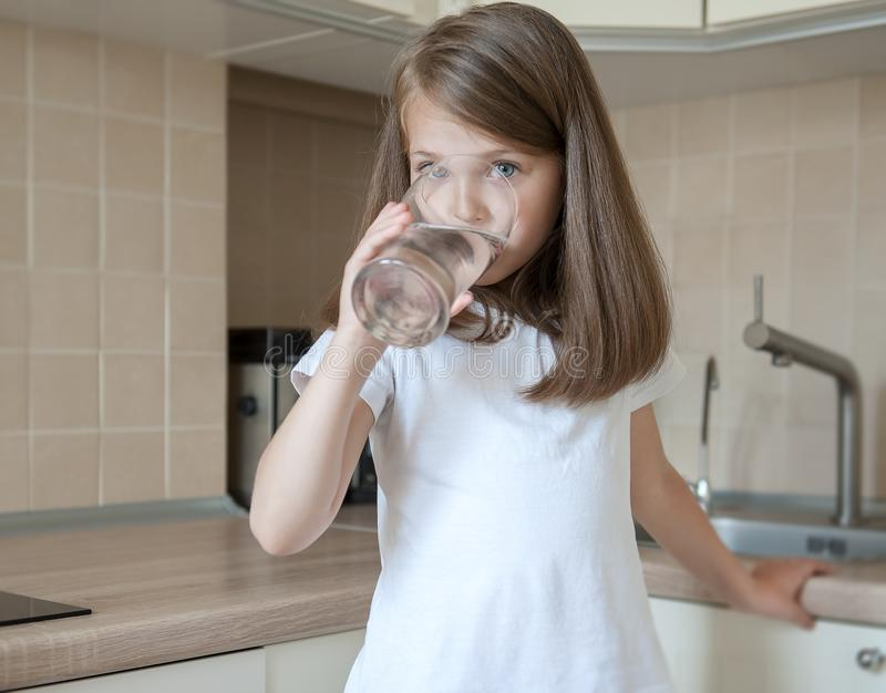 Happy adorable little girl drinking water in the kitchen at home. Caucasian kid  with long brown hair holding transparent glass. In her hand. Indoors. Healthy royalty free stock photography