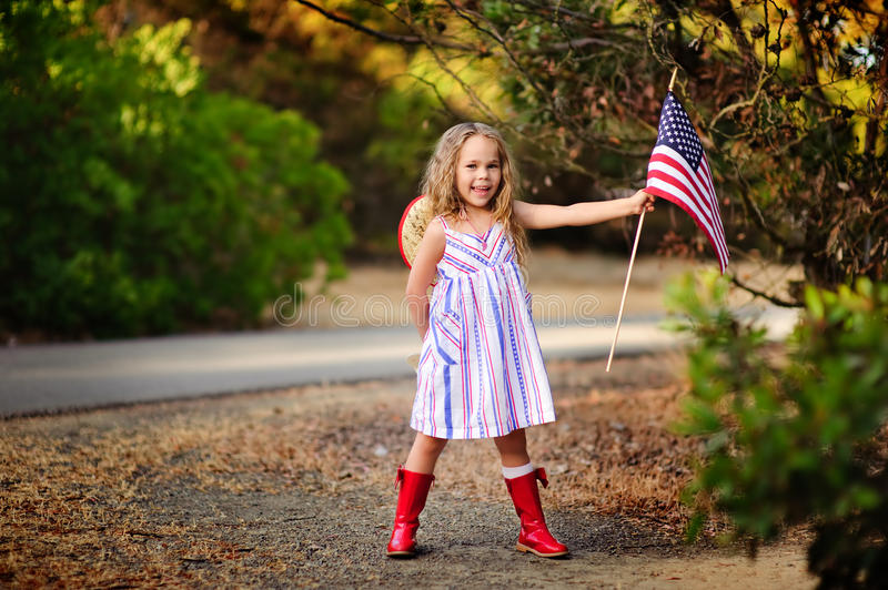 Happy adorable little girl smiling and waving American flag outs royalty free stock photo