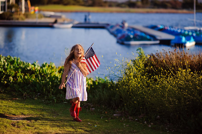 Happy adorable little girl smiling and waving American flag outs. Ide, her dress with strip and stars, cowboy hat. Smiling child celebrating 4th july stock photography
