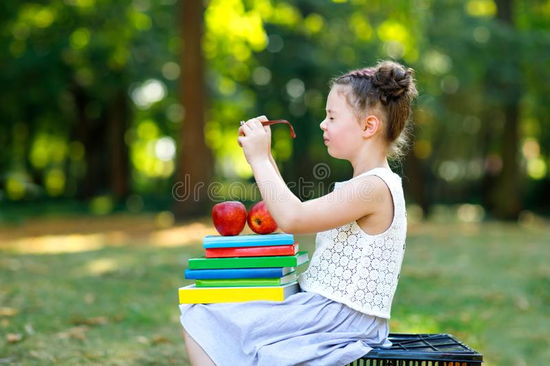 Happy adorable little kid girl reading book and holding different colorful books, apples and glasses on first day to stock photography