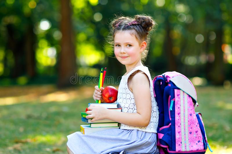 Happy adorable little kid girl reading book and holding different colorful books, apples and pencils on first day to royalty free stock photos