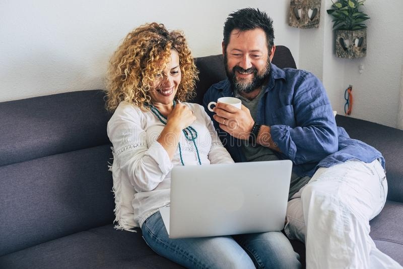 Happy adult aged couple caucasian people at home with personal laptop computer and internet connection - together in indoor. Leisure activity with technology stock image