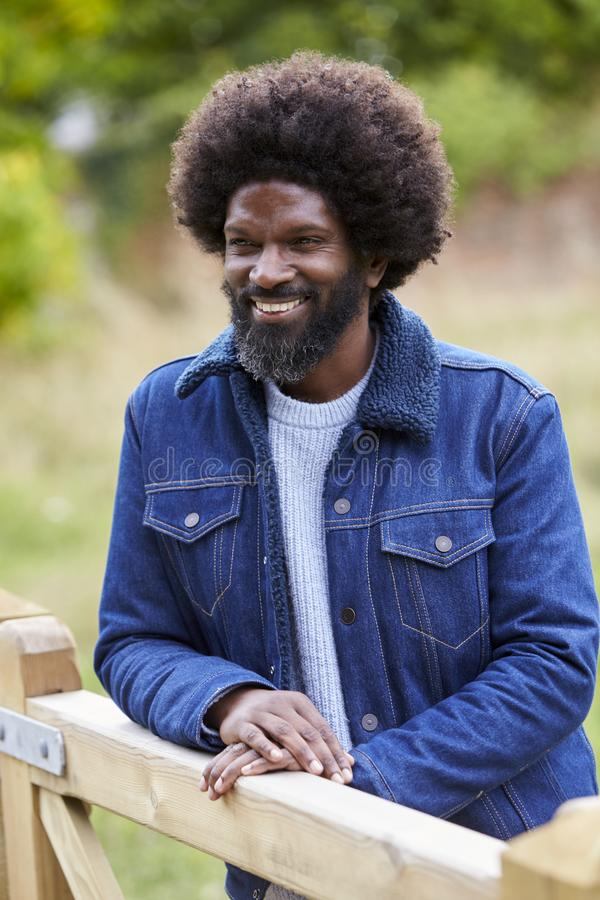 Happy adult black man leaning on a wooden fance in the countryside smiling, close up royalty free stock images
