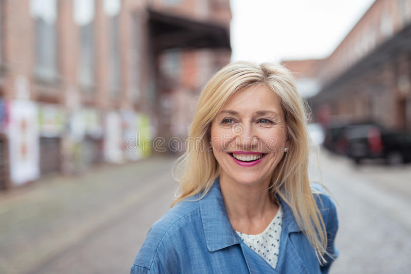 Happy Adult Blond Woman Laughing at the Street royalty free stock photography