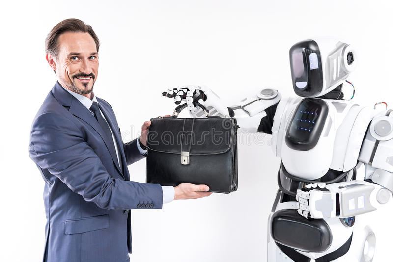 Happy adult businessman is standing with robot and holding portfolio royalty free stock photos