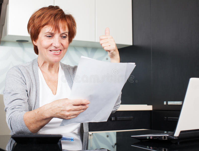 Happy adult businesswoman. Happy businesswoman with documentation in office royalty free stock images
