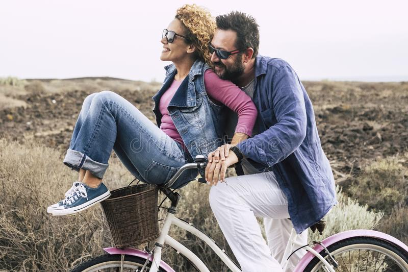 Happy adult caucasian, couple having fun with bicycle in outdoor leisure activity. concept of active playful people with bike. During vacation - everyday joy royalty free stock images