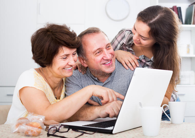 Happy adult daughter showing documents to her parents. Happy adult daughter showing documents on laptop to her mature parents at home royalty free stock photo