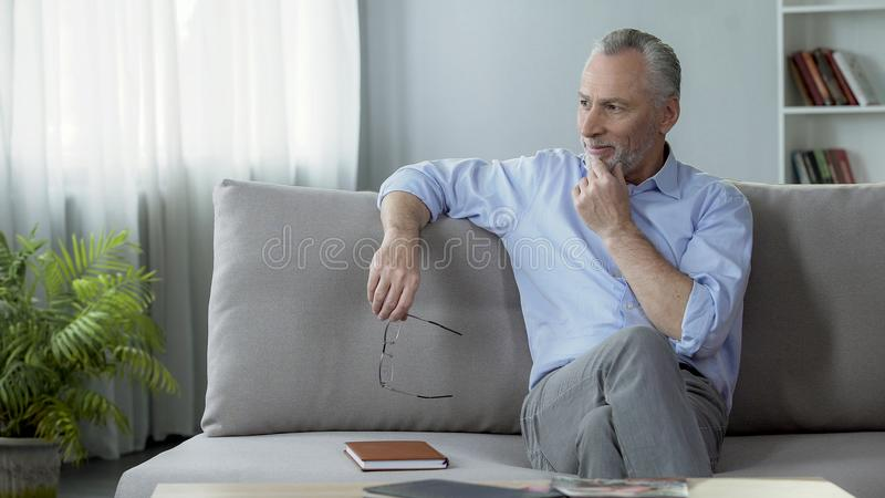 Happy adult male sitting on couch and remembering last summer vacation, leisure stock photography