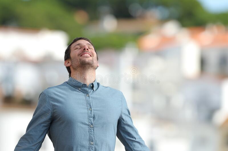 Happy adult man breaths deeply fresh air in a rural town stock images