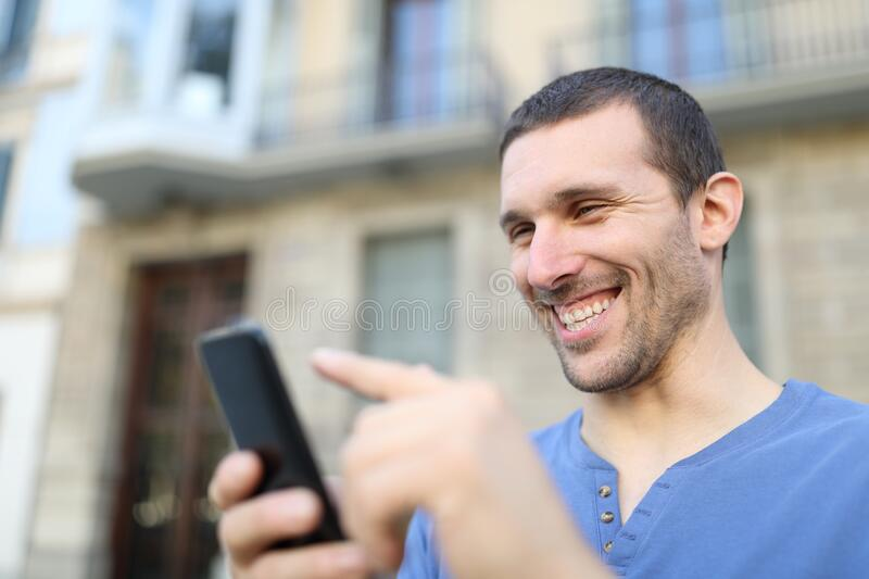 Happy adult man browsing phone content in the street stock photos